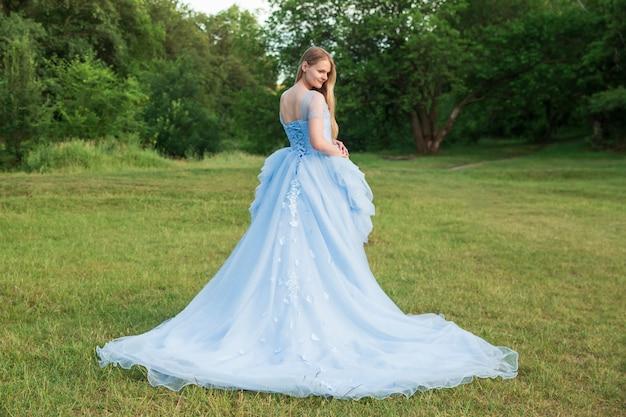 Femme aux cheveux blonds vêtue d'une belle robe bleue à manches longues en plein air Photo Premium