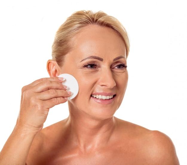 Femme aux épaules nues nettoyant le visage à l'aide d'un disque de coton. Photo Premium