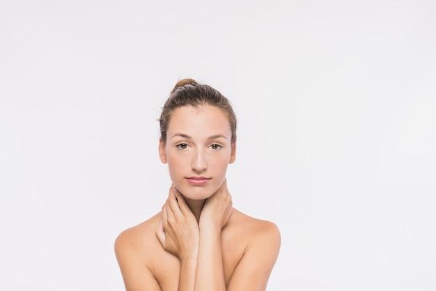 Femme aux épaules nues touchant le cou Photo gratuit