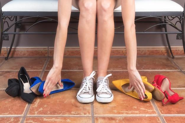 Femme aux jambes fines et parfaites, choisissant des baskets confortables plutôt que des chaussures à talons hauts inconfortables. Photo Premium