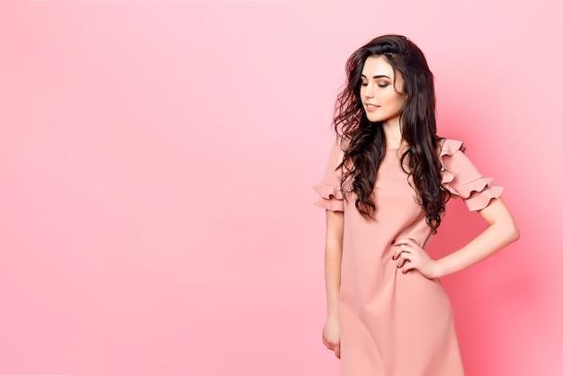 Femme aux longs cheveux bouclés dans une robe rose. Photo Premium