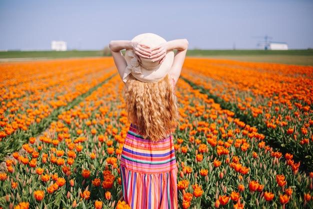 Femme aux longs cheveux roux vêtue d'une robe rayée, debout à l'arrière sur le champ de tulipes colorées. Photo Premium