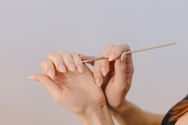 Une femme aux mains bien coiffées se couvre les ongles avec du gel-vernis à l'aide d'un pinceau fin sur fond blanc. Photo Premium