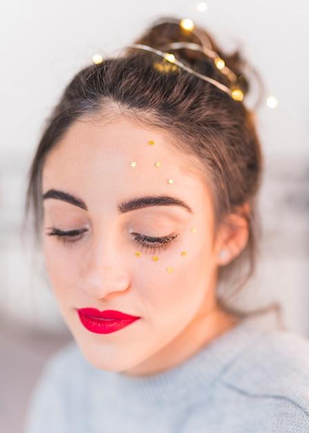 Femme aux petites étoiles étoilées sur le visage Photo gratuit