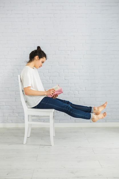 Femme aux pieds nus, appréciant la lecture sur la chaise Photo gratuit