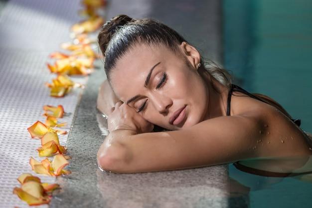 Femme aux yeux fermés dans la piscine Photo Premium