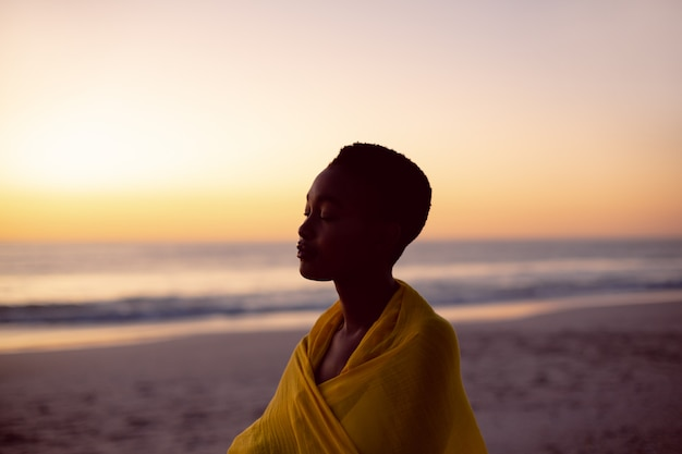 Femme Aux Yeux Fermés, Enveloppée Dans Un Foulard Jaune Sur La Plage Photo gratuit
