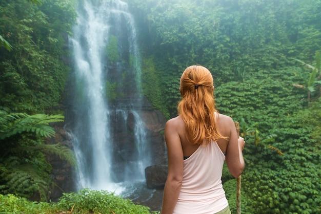 Femme Aventurière Regarde La Cascade Photo gratuit