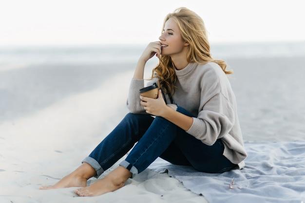 Femme Aveugle Pensif En Jeans Assis Dans Le Sable Et Regardant La Mer. Portrait En Plein Air De Femme Caucasienne Détendue, Boire Du Café à La Plage. Photo gratuit