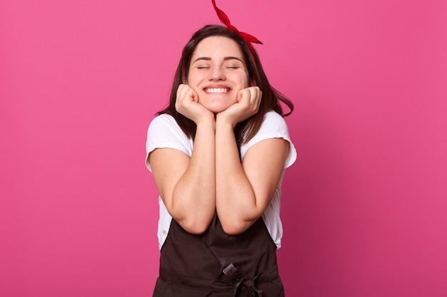 Femme Ayant Une Expression Faciale Agréable, Mettant Ses Mains Sur Le Visage, Fermant Les Yeux, Souriant Sincèrement Photo Premium