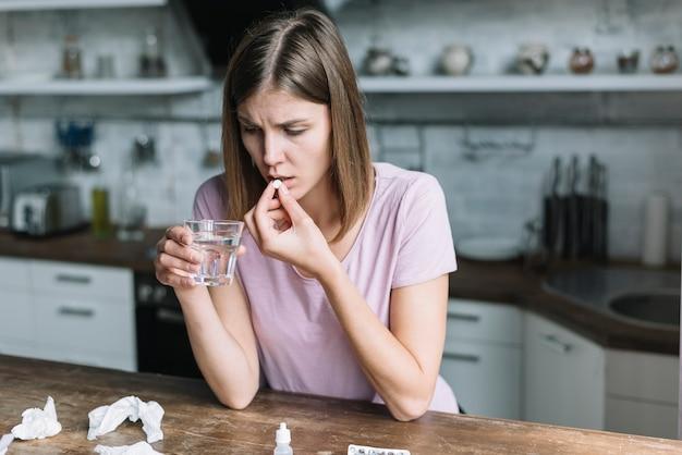 Femme ayant de la fièvre prenant des médicaments à la maison Photo gratuit