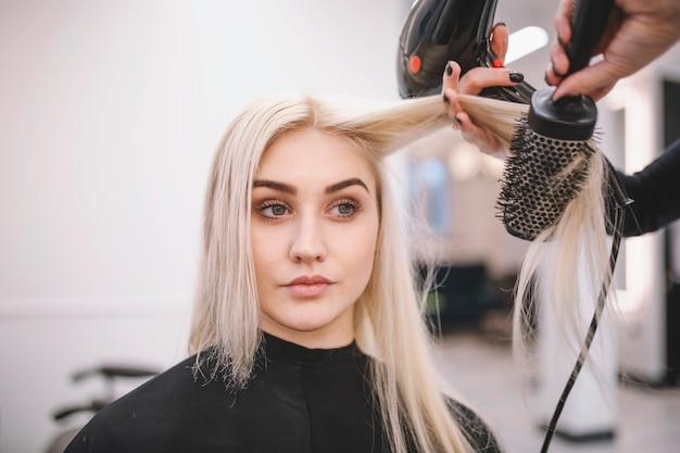 Femme ayant une procédure de style dans le salon Photo gratuit