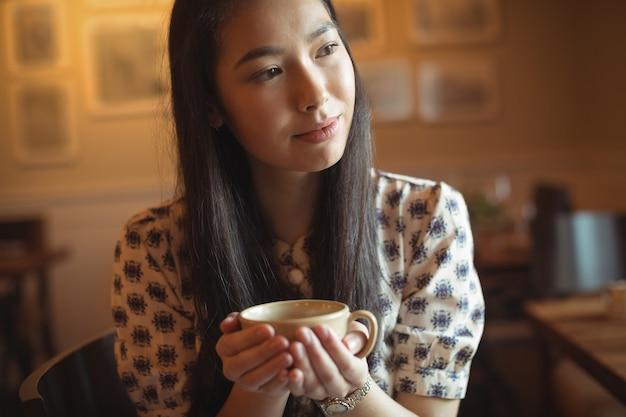 Femme Ayant Une Tasse De Café Au Café Photo gratuit