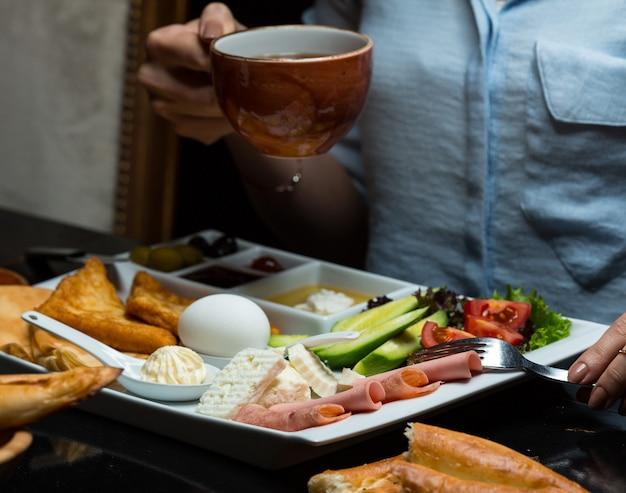 Femme ayant une tasse de thé un petit-déjeuner Photo gratuit