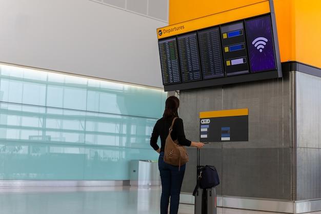 Femme avec bagage à main en regardant les informations de vol dans l'aéroport. Photo Premium