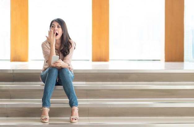 Femme bâillant en utilisant un smartphone Photo Premium