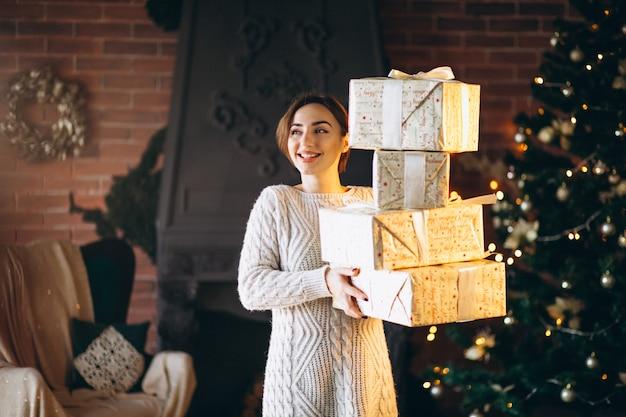 Femme avec beaucoup de cadeaux devant l'arbre de noël Photo gratuit