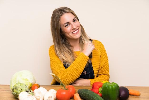 Femme avec beaucoup de légumes célébrant une victoire Photo Premium