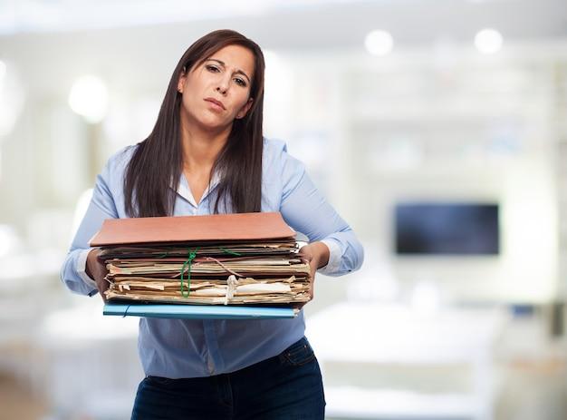 Femme avec beaucoup de papiers et dossiers Photo gratuit
