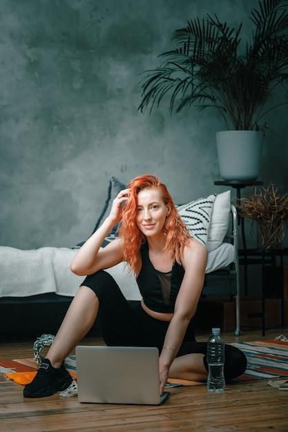 La Femme De Beauté Fait Du Sport à La Maison. Enthousiaste Femme Sportive Aux Cheveux Rouges Assis, Souriant Et Regardant Dans Un Ordinateur Portable, Shootting Blog Dans La Chambre Photo Premium
