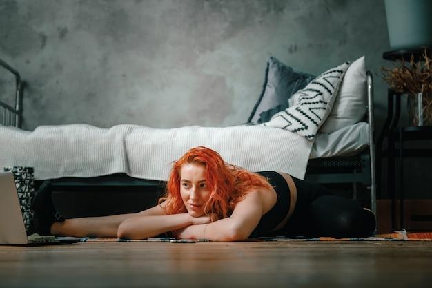 La Femme De Beauté Fait Du Sport à La Maison. Enthousiaste Femme Sportive Aux Cheveux Rouges S'étire Jusqu'à La Jambe Et Regarde Dans Un Ordinateur Portable, Blog De Tir Dans La Chambre Photo Premium