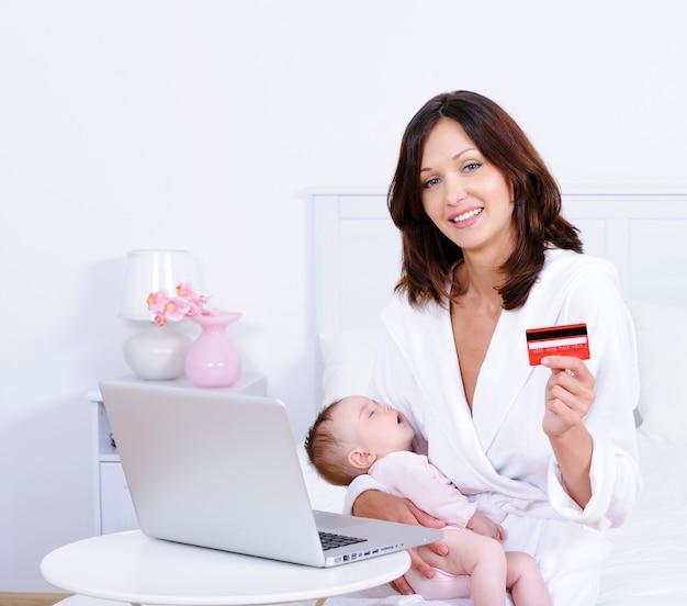 Femme Avec Bébé, Carte De Crédit Et Ordinateur Portable à La Maison Photo gratuit