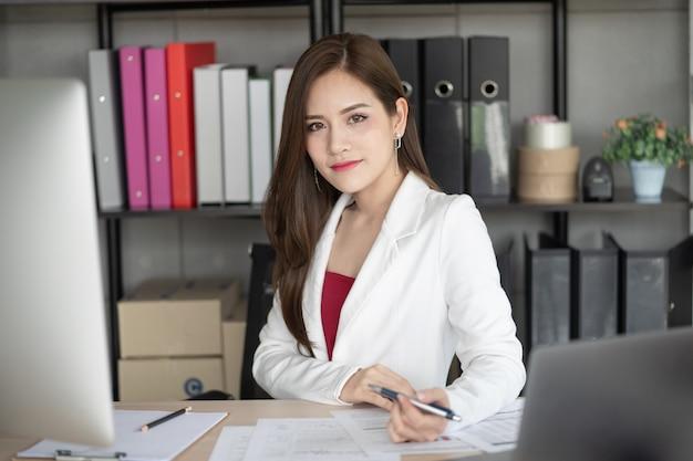 Une femme belle et intelligente qui travaille est assise à son bureau dans le bureau. Photo Premium
