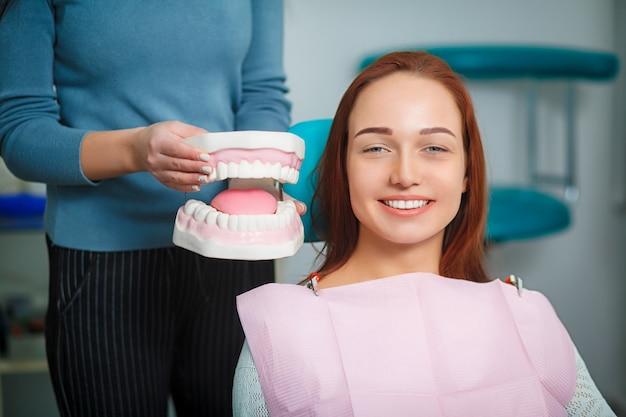 Femme Avec De Belles Dents Blanches, Assis Sur Un Fauteuil Dentaire. Photo Premium