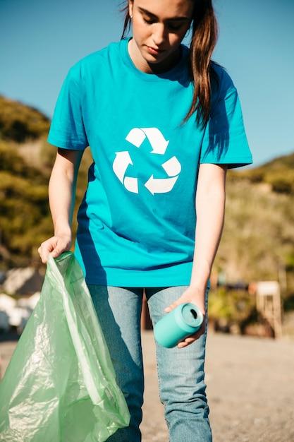Femme bénévole collecte des ordures à la plage Photo gratuit