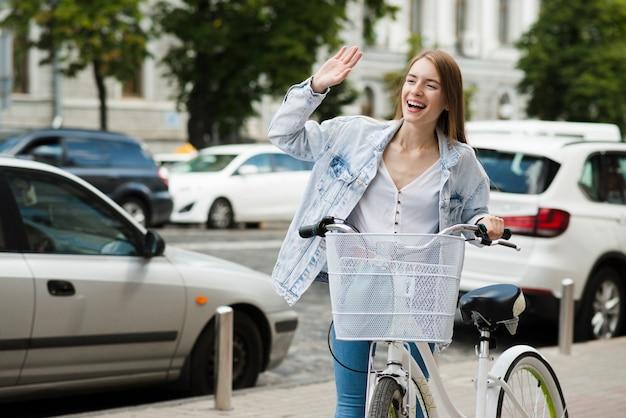 Femme, bicyclette, agitant Photo gratuit