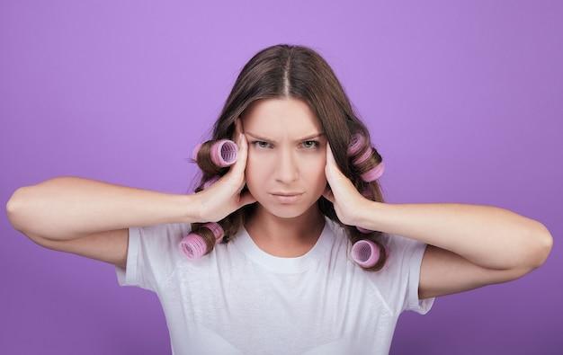 Une femme en bigoudis roses en arrière-plan semble droite. Photo Premium