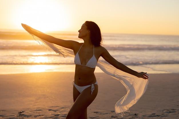 Femme en bikini en agitant un foulard sur la plage Photo gratuit