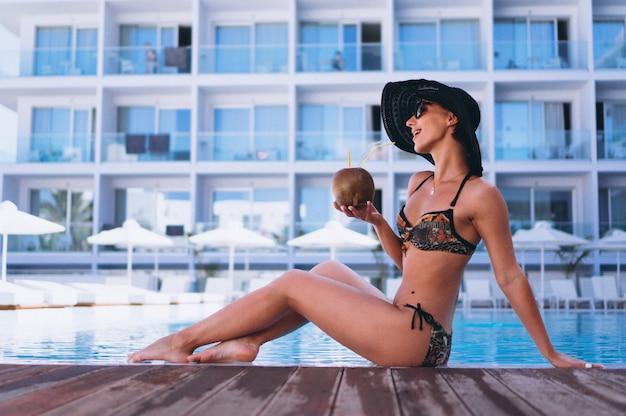 Femme, bikini, boire, lait coco, par, les, piscine Photo gratuit