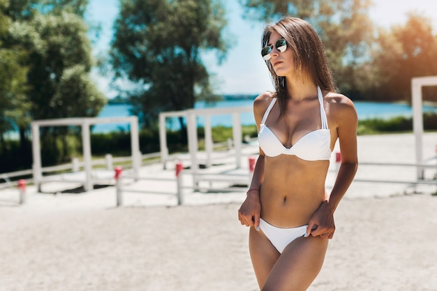 Femme en bikini, gardant les mains sur les hanches Photo gratuit