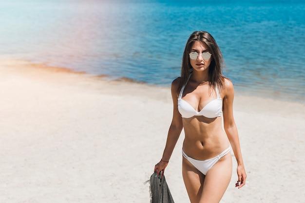 Femme en bikini marchant loin de la mer Photo gratuit