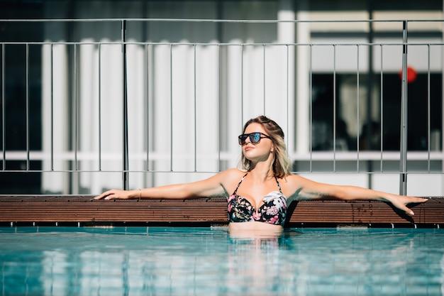 Femme En Bikini Noir Au Bord De La Piscine Dans Un Paysage D'été Photo gratuit