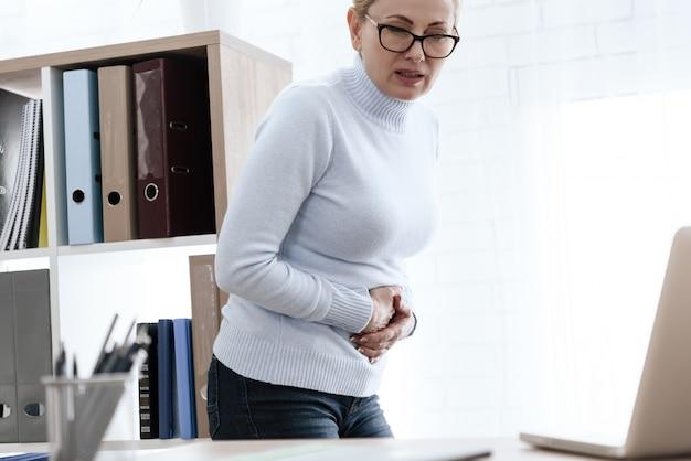 Une femme blanche a mal au ventre au travail. Photo Premium
