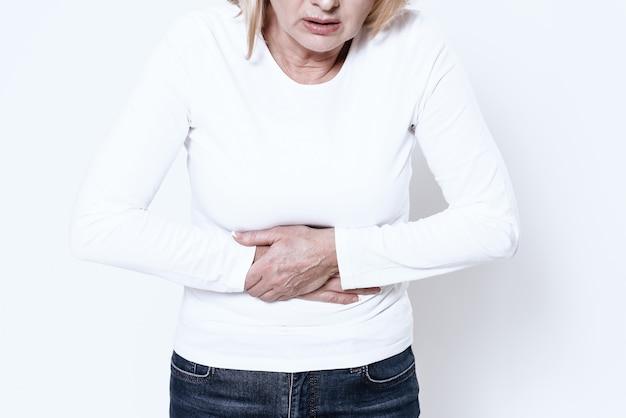 Une femme blanche a mal au ventre en studio. Photo Premium
