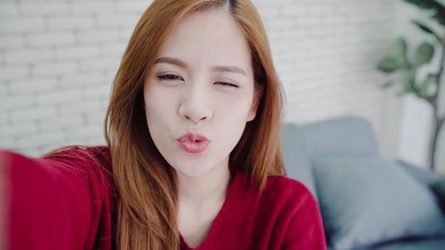 Femme blogueuse asiatique utilisant un smartphone enregistrant une vidéo vlog dans le salon à la maison Photo gratuit
