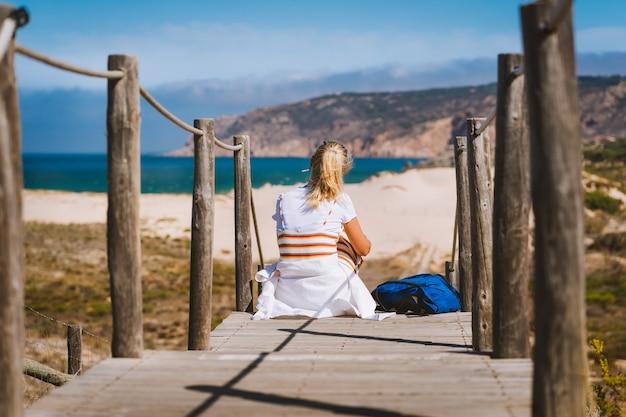 Femme Blonde Adulte Touriste Assis Sur Le Chemin Menant à La Plage De Praia Do Guincho. Photo Premium