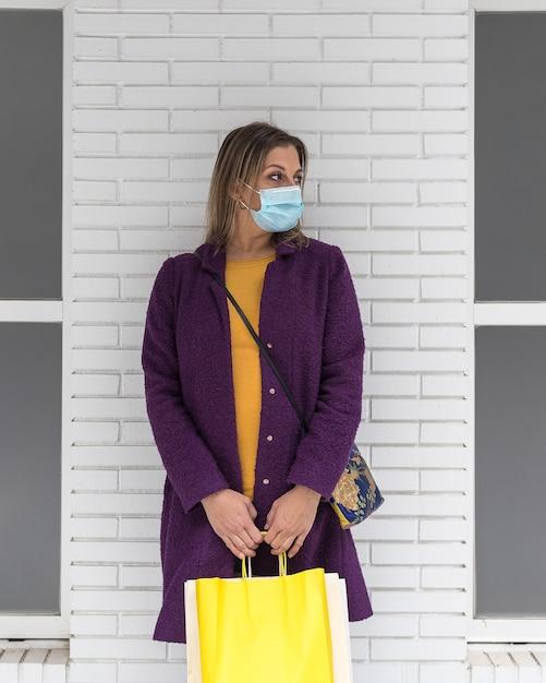 Une Femme Blonde D'âge Moyen Portant Un Masque Chirurgical Et Tenant Des Sacs à Provisions Photo Premium