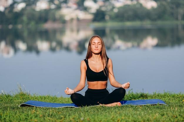 Femme Blonde Assise En Méditation Pose En Plein Air. Photo Premium
