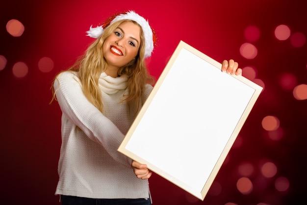 Femme Blonde Avec Un Chapeau De Père Noël Tenant Tableau Blanc Photo gratuit