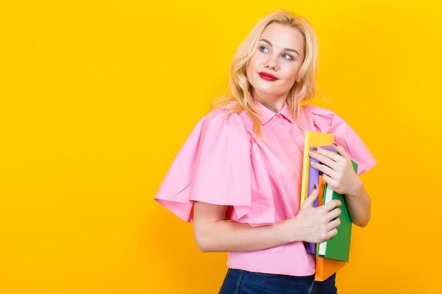 Femme blonde en chemisier rose avec une pile de livres Photo Premium