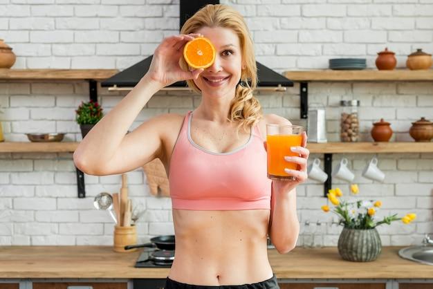 Femme blonde dans la cuisine avec des fruits Photo gratuit