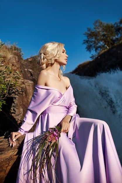 Femme Blonde Dans Une Longue Robe Rose Assise Sur Une Pierre Près De La Cascade. Magnifiques Cheveux Longs Beau Sourire Sur Le Visage De La Fille Photo Premium