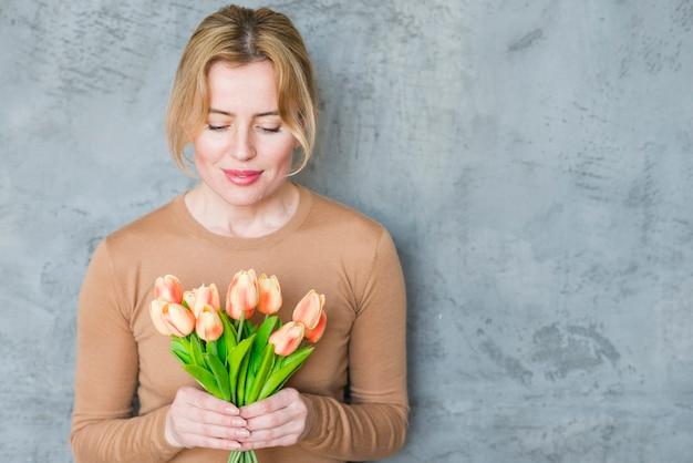 Femme blonde debout avec bouquet de tulipes Photo gratuit