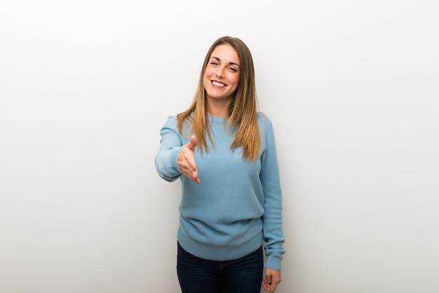 Femme blonde sur fond blanc isolé se serrant la main pour la fermeture d'une bonne affaire Photo Premium