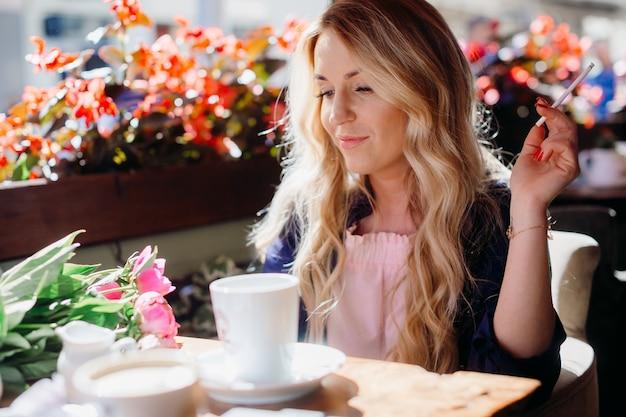Femme blonde fume un cigare boire du café dans le café Photo gratuit