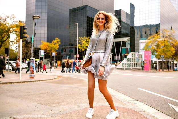 Femme Blonde Heureuse Sortie Sautant Dansant Et S'amusant Dans La Rue Près D'un Bâtiment Moderne, Baskets élégantes Et élégantes En Argent, Sac De Luxe Et Lunettes De Soleil, Touriste Heureux à New York. Photo gratuit